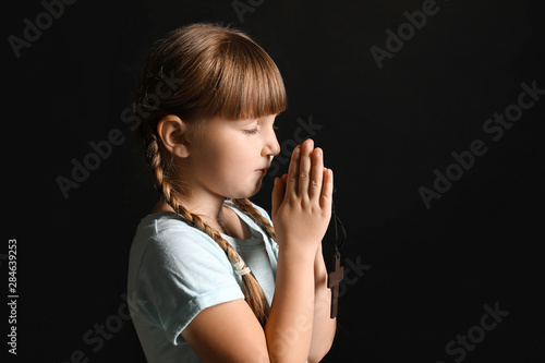 Photo Little girl praying on dark background