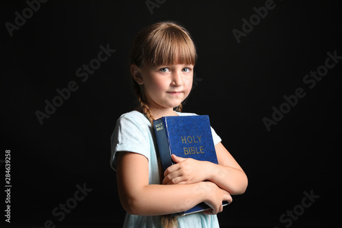 Photo Little girl with Bible on dark background