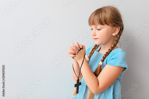 Little girl praying on light background Canvas Print