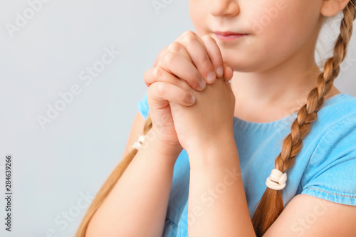 Little girl praying on light background, closeup Canvas Print