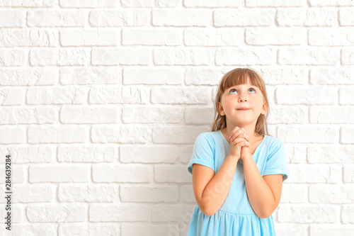 Little girl praying on white background Canvas Print