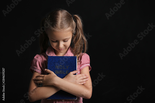 Photo Cute little girl with Bible on dark background