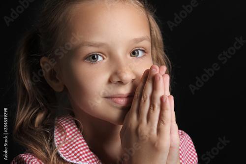 Praying little girl on dark background Canvas Print