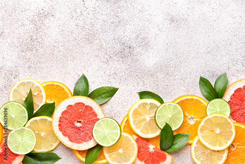 Different citrus fruits on grey background