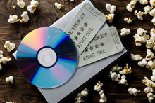 Movie Tickets, DVD Or Blu Ray Disc And Popcorn On Dark Wooden Table Background. Home Theatre Movie Or Series Night Concept. Flat Lay Top View From Above