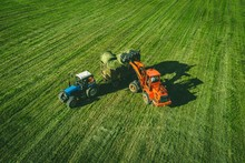 Aerial View Of Tractor With Round Baler Rolling Bales Of Straw On Harvested Field