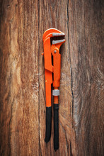 Heavy-duty Orange Pipe Wrench On Vintage Wooden Table Under Dark Dramatic Moody Lighting.