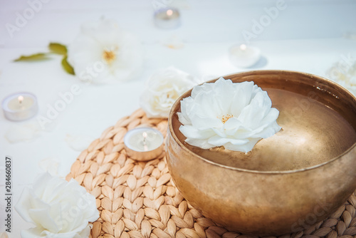 Photo Close up Tibetan singing bowl with floating in water rose inside