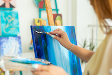 Art Class, Drawing And Creativity Concept - Female Student Sitting In Front Of Easel With Palette And Paintbrush, Close-up