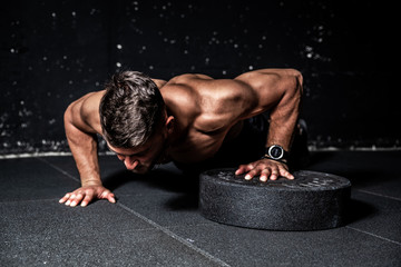 Young strong sweaty focused fit muscular man with big muscles performing push ups with one hand on the barbell weight plate for training hard core workout in the gym