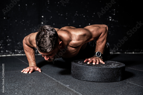 Fotografiet  Young strong sweaty focused fit muscular man with big muscles performing push up