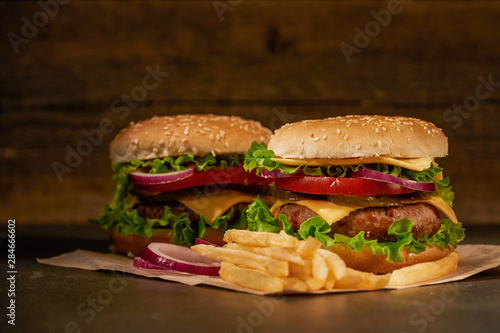 Keuken foto achterwand Snack homemade hamburger with French fries tomatoes and cheese and herbs and onions