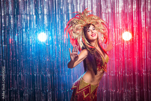 Fototapeta Carnival, dancer and holiday concept - Beauty brunette woman in cabaret suit and headdress with natural feathers and rhinestones