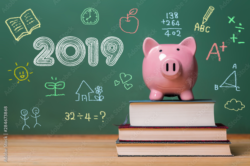 Photo  Year 2019 text with pink piggy bank on top of books with chalkboard