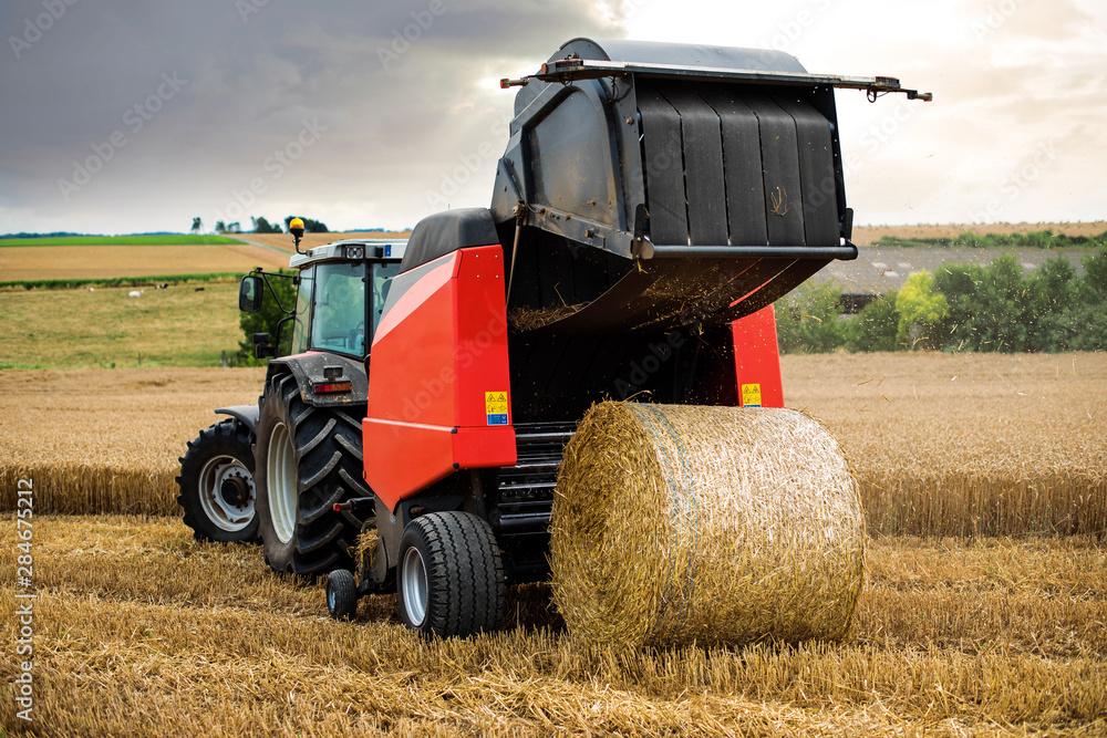 Fototapeta farmer in fields making straw bales