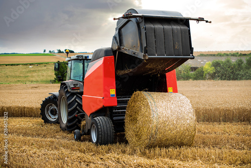 Fototapeta farmer in fields making straw bales obraz