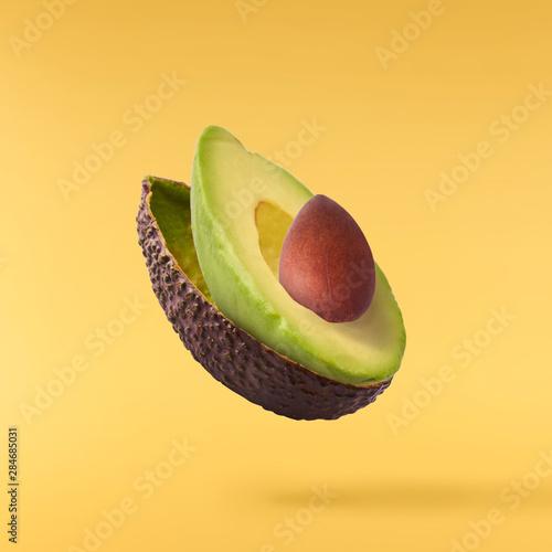 Fresh ripe avocado with leaves falling in the air. Fototapeta