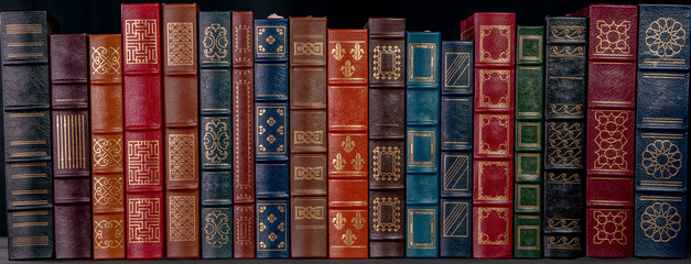 A stack of beautiful leather bound books with golden decoration against a bla...