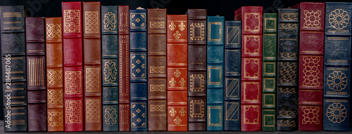 Fotografía A stack of beautiful leather bound books with golden decoration against a black background
