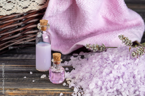 Lavender spa setting: salt, essential oil and dried flowers natural spa products and decor for bath on dark background.