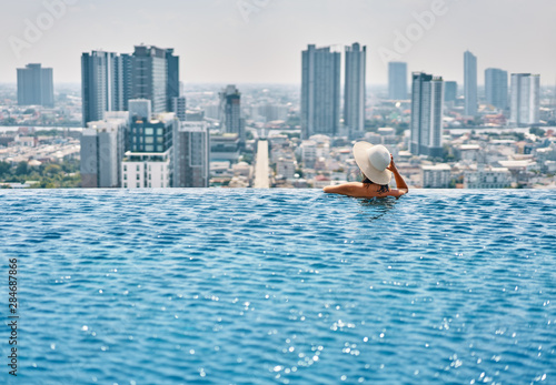 Obraz Back view of young woman in hat relaxing in swimming pool on the roof top of hotel and enjoy cityscape - fototapety do salonu