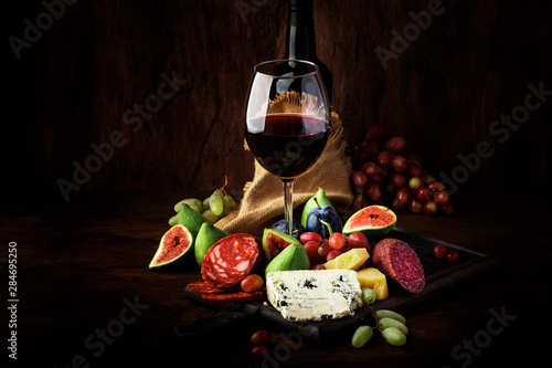 Fototapeta Red wine glass and appetizers, cheese, salami, figs, grapes, vintage wooden table background, selective focus, copy space obraz