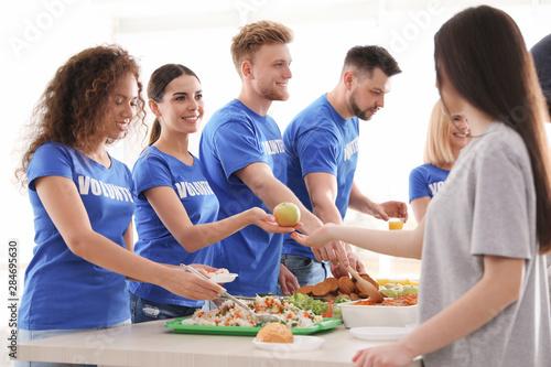 Fototapeta Volunteers serving food to poor people indoors obraz