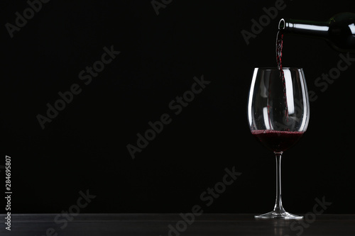Pouring wine from bottle into glass on table against black background, space for text