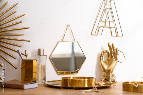Fototapeta Composition with gold accessories on dressing table near white wall obraz