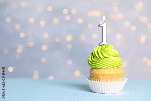 Birthday cupcake with number one candle on table against festive lights, space f Canvas Print