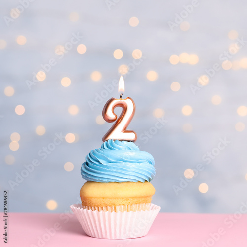Birthday cupcake with number two candle on table against festive lights