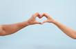 Leinwandbild Motiv Happy couple making heart with their hands against blurred landscape
