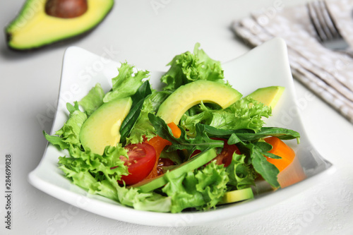 Delicious avocado salad in bowl on white table