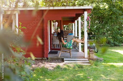 Young woman on porch of summer house Fototapeta