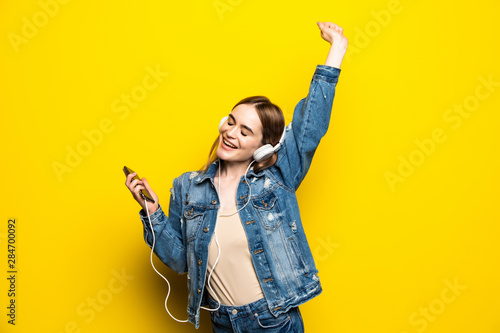 Happy cheerful woman wearing headphones listening to music from smartphone studio shot isolated on yellow background