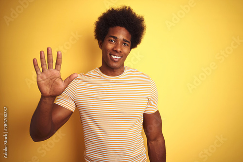American man with afro hair wearing striped t-shirt standing over isolated yellow background showing and pointing up with fingers number five while smiling confident and happy Tableau sur Toile