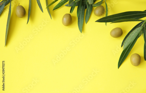 Flat lay. Organic green olives with olive leaves on a yellow background. Healthy food. Mediterranean diet. Poster, pattern, background, texture, postcard. With copy space for text. Top view.