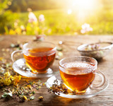 Cups of herbal tea with various herbs at sunset - 284711686