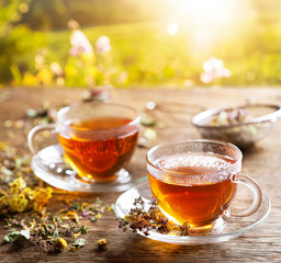 Cups of herbal tea with various herbs at sunset