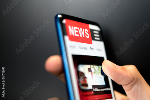 Fototapeta A man holding mobile smart phone with news on screen. Newspaper online portal in browser. obraz