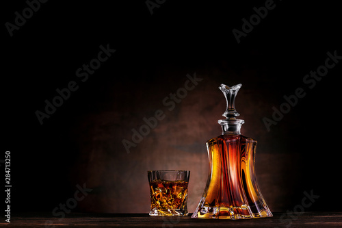 Photo Glass of whiskey with ice and decanter on dark wood background