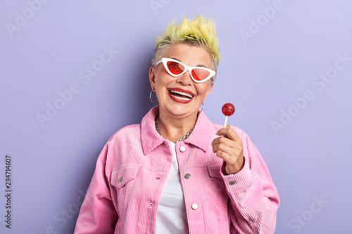 funny playfull cheerful old woman in pink stylish suit holding chup chups and posing to the camera Canvas Print