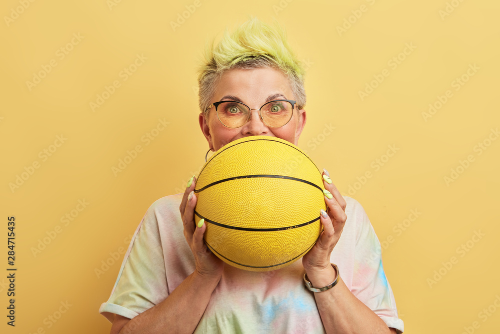 Fototapety, obrazy: happy excited glamour cool senior holding basketball - isolated on yellow background. lifestyle, interest, hobby, sport fan
