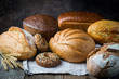 Assortment of fresh baked bread and buns on wooden table background