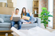 Young beautiful couple relaxing sitting on the sofa of new house using computer laptop doing ok sign with fingers, excellent symbol