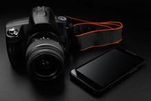 Professional Digital Slr Camera And Smartphone On Black Background