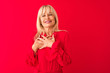 canvas print picture - Middle age woman wearing elegant shirt standing over isolated red background smiling with hands on chest with closed eyes and grateful gesture on face. Health concept.
