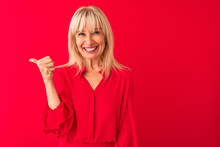 Middle Age Woman Wearing Elegant Shirt Standing Over Isolated Red Background Smiling With Happy Face Looking And Pointing To The Side With Thumb Up.