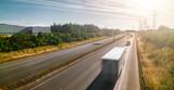 Fototapeta Kawa jest smaczna - Lots of Trucks and cars on a Highway - transportation concept