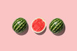 canvas print picture - Three halves of watermelon in a row isolated on pink background.